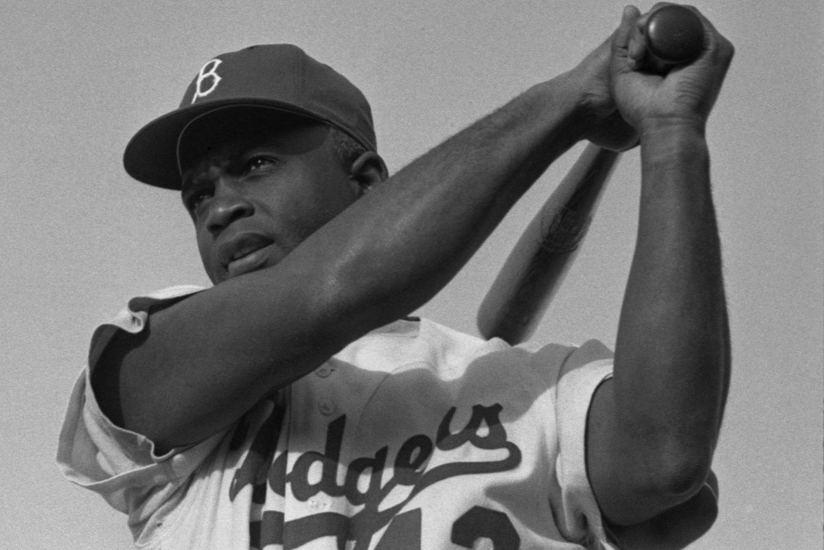 Jackie Robinson swinging a bat in Dodgers uniform, 1954. (Photo credit: Wikimedia)